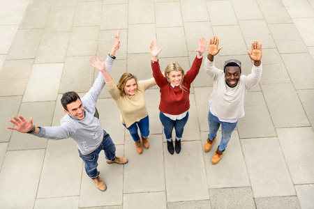 Group of different countries best friends put hands up together like one work team spirit. Top view of multiracial happy people with raised arms outdoor and sharing time. Students friendship concept.