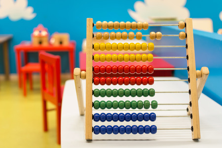 Educational toy for babies inside colorful room with red chairs and blue wall - Multicolor wooden abacus on the white desk - Concept of education learning and teaching - Main focus on red balls