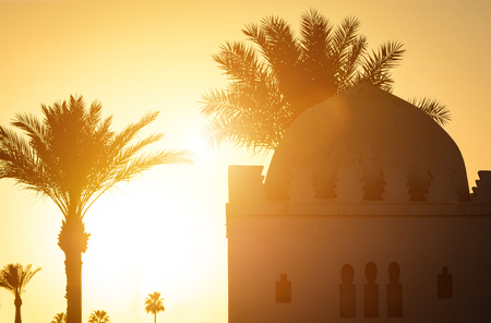 Beautiful sunset moment with Islamic church, palms at background. Silhouette of palm trees with old religious building in Marrakesh town with gold sun rays and lens flare. Wanderlust travel concept. 免版税图像