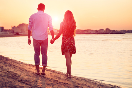 Rear view of happy couple standing against a beach side in summer. Two lovers in vacation in an idyllic nature scene sharing positive feelings and emotions. Magic moments of loving hearts.