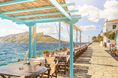 Summer photo with panoramic view from Aegina island in Greece. Beautiful place for making lunch on seafront with wooden roof of bar and restaurant. Magic moment during sunny day for chilling and relax 免版税图像