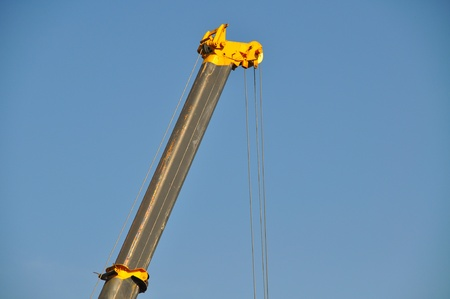 Closeup of yellow jib crane against blue sky photo