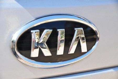 Kia logo on a wet gray car