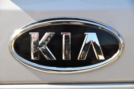 Kia logo on a wet gray car