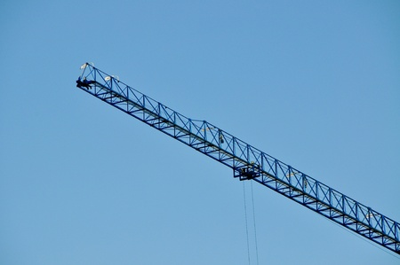Closeup of blue jib crane against blue sky photo
