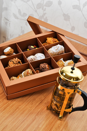 Delicious cookies candies in a box and herbal tea photo