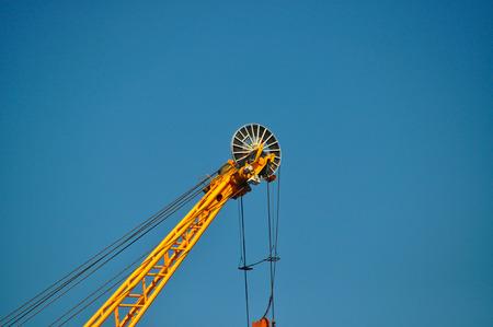 Closeup of yellow jib crane against blue sky photo