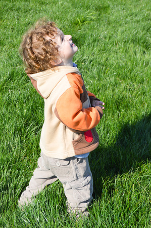child looking up: Child looking up on the grass Stock Photo