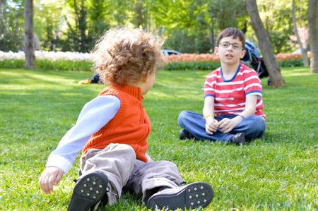 hermanos jugando: Dos hermanos felices jugando en la hierba Foto de archivo
