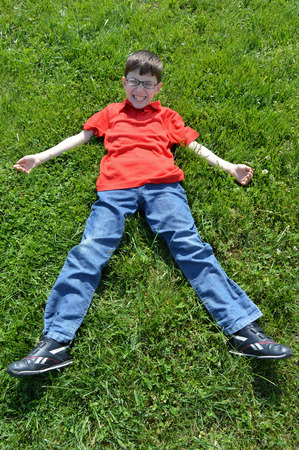 felicity: Young boy lying on the green grass