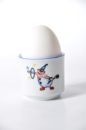 egg cup: A fresh white egg and egg cup