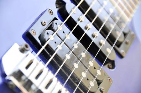 Part of an electric guitar with pickup and strings