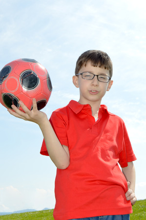 8 year old: 8 year old boy and red ball in hand