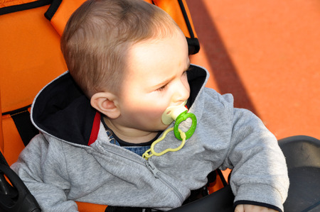 There's a cute baby pacifier in his mouth Stock Photo - 55465824