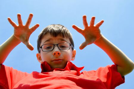 felicity: Young boy doing hand signs and blue sky in the background Stock Photo