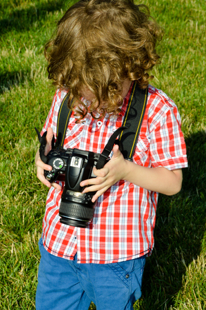 blond haired: Very cute blond haired little boy photographer Stock Photo