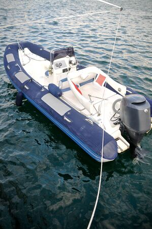 inflatable boat: Modern inflatable boat with engine in the sea near shore