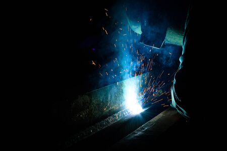 laboring: Welder uses torch to make sparks during manufacture of metal equipment