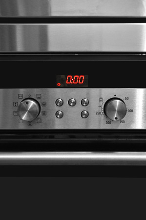 The modern kitchen has an oven and the control panel