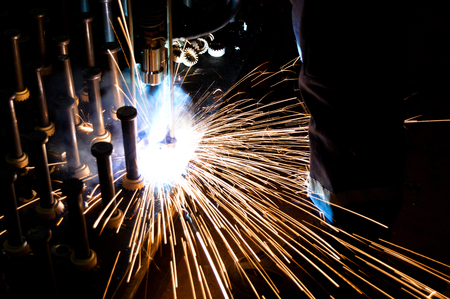 Welder uses torch to make sparks during manufacture of metal equipment