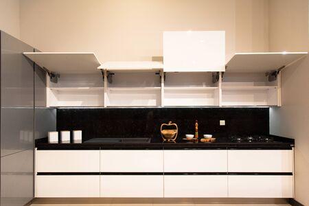 Interior of luxurious modern kitchen, white grey cabinets and black granite