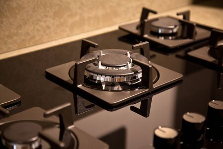Interior of luxurious modern kitchen equipment and black glass ceramic built-in gas oven