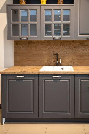Interieur van luxe houten moderne keukenapparatuur en grijze kasten