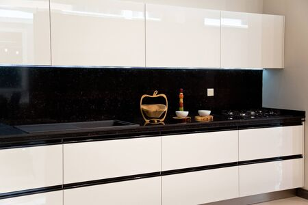 Interior of luxurious modern kitchen, white cabinets and black granite