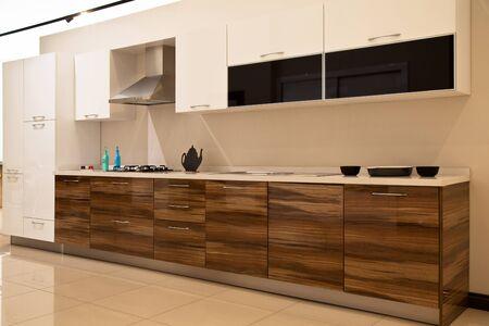 Interior de lujosos y modernos equipos de cocina y gabinetes blancos de nogal Foto de archivo