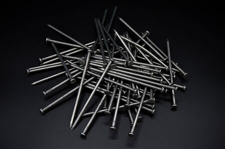 A lot of construction iron nails, industrial parts, isolated on black background 版權商用圖片
