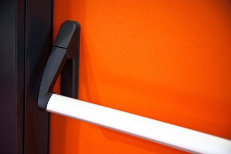 Emergency exit door. Closed up latch and orange door handle of emergency exit. Push bar and rail for panic exit Imagens