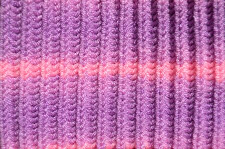 Pattern fabric made of wool. Handmade knitted fabric purple and pink wool background texture Фото со стока