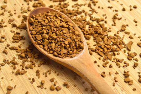 Fresh granules of instant coffee grains, in wooden spoon, on wooden bamboo background