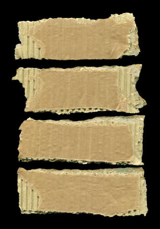 Brown and beige corrugated cardboard pieces, isolated on black background Banco de Imagens