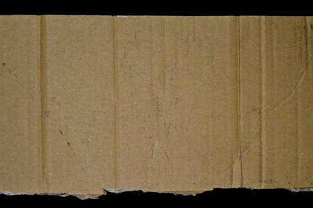 Brown and beige corrugated cardboard, isolated on black background