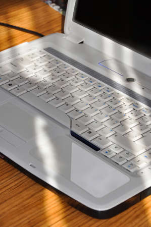 White laptop isolated on a wooden table, a white color laptop