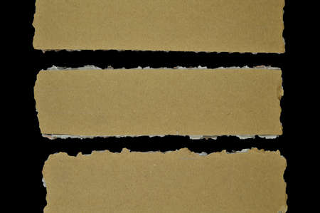 Brown and beige corrugated cardboard pieces, isolated on black background