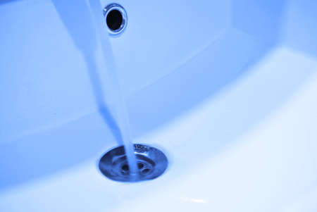 Drain in a white clean sink, background, close-up