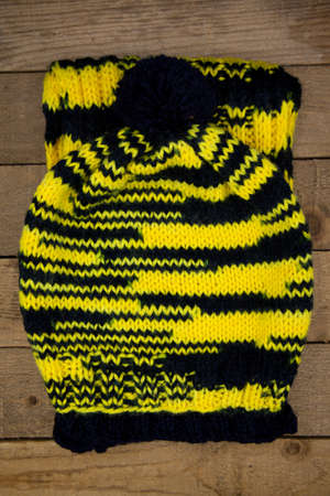 Handmade wool knitted winter hat and scarf isolated on old wood background