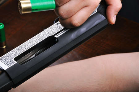 Shotgun bullet and trigger mechanism isolated on wood background, hunting shotgun detail