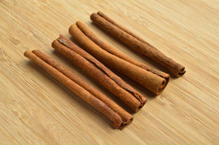 Dried long brown cinnamon sticks, aromatic spice, on wooden background