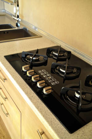 Modern clean kitchen and black glass ceramic built-in gas oven detail Stock Photo