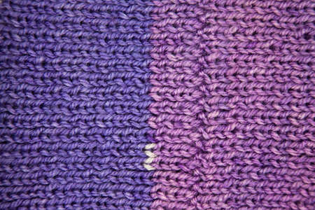 Pattern fabric made of wool. Handmade knitted fabric purple and blue wool background texture