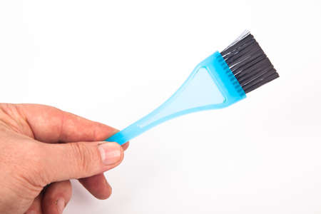Blue plastic bristle brush used for hair coloring in hairdressers
