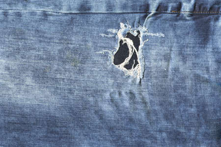Seam blue denim cotton ripped jeans fabric texture background and wallpaper