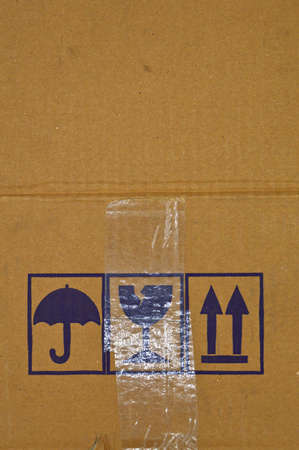 Brown and beige colored corrugated cardboard and warning signs detail