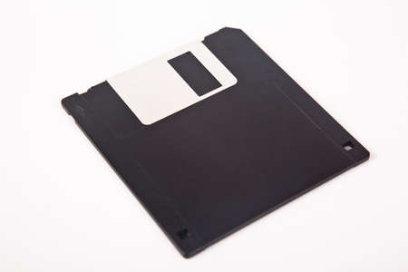 Old computer and data storage technology, black plastic magnetic floppy disk 3½ inches, isolated on white background