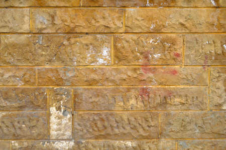Sturdy yellow and beige cut stone wall, good for backgrounds, seamless lined up