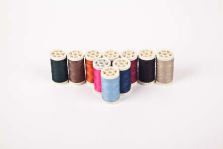 Spools and bobbins of thread for sewing in different colors, isolated on white background