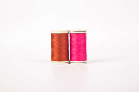 Spools and bobbins of thread for sewing in different pink orange, isolated on white background